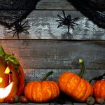 halloween jack o lantern lit at night with pumpkin bottom border against a rustic old wood background