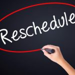 woman hand writing reschedule on blank transparent board with a marker isolated over black background. stock photo